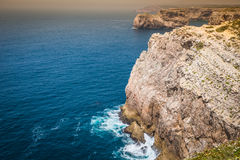 High cliffs and blue ocean at Cabo Sao Vicente on coast of Portu Stock Images