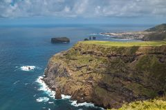 Cliffs in the north of Sao Miguel, Azores Islands. High cliffs on the north of island Sao Miguel. White foam at the shore line. City on another cape in the royalty free stock image