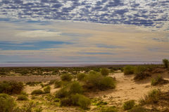High cloud over south Lake Eyre. The salt pan sparkles in early morning light over South Lake Eyre Stock Photos