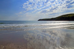 High clouds above the headland, reflected in the wet sands of Aberdaron Beach and bay Stock Image