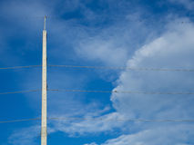 High concrete electric pole. Tall and high concrete electric pole with power line cables and have birds on them, against the blue sky and some cloud. Electric Stock Photo