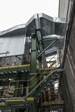 High, concrete industrial chimney and dust collector on a winter royalty free stock photography