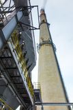 High, concrete industrial chimney and dust collector on a winter. High, concrete industrial chimney and dust collector on a foggy winter day royalty free stock photos