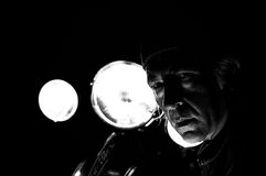 High contrast biker in front of headlights. High contrast grainy image of male biker, back lit by headlights staring at viewer Royalty Free Stock Photos