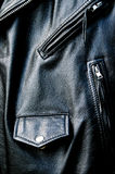 High contrast black leather biker jacket detail. High contrast close up of black leather biker jacket showing zippered pockets and coin pocket with snap button Stock Photo