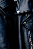 High contrast black leather biker jacket up close. High contrast close up of black leather biker jacket showing zipper, shoulder and snap collar and lapel in Stock Photography