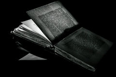High contrast black and white image of an old book on black reflective surface Stock Photos