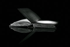 High contrast black and white image of an old book on black reflective surface Royalty Free Stock Photography