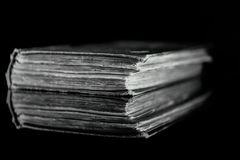 High contrast black and white image of an old book on black reflective surface Stock Photography