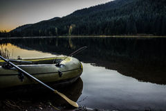 High contrast fishing boat awaiting takeoff. Inflatable fishing boat on the shore with paddles and fishing gear at Trillium Lake, Oregon Stock Photo