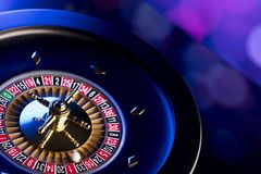 Casino theme. Place for typography. High contrast image of casino roulette. Blue bokeh background. Place for text royalty free stock photography