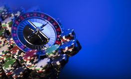 Casino concept. Place for typography. High contrast image of casino roulette, poker chips. Blue light and place for text stock images