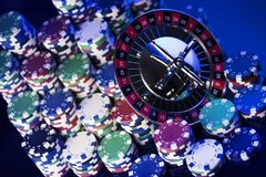Casino concept. Place for typography. High contrast image of casino roulette, poker chips. Blue light and place for text stock photos