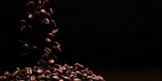 High contrast image of coffee beans. High contrast image of coffee beans being dropped onto pile with black background Royalty Free Stock Image