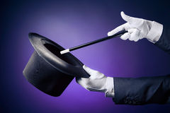 High contrast image of magician hand with magic wand. Magician hand with magic wand and hat royalty free stock image
