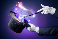 High contrast image of magician hand with magic wand. Magician hand with magic wand and hat
