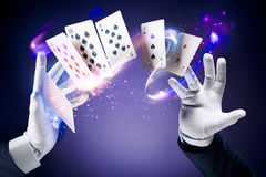High contrast image of magician making card tricks. Magician hands with magic cards stock image