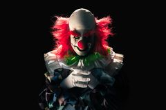 Scary clown on a dark background. High contrast image of a scary clown on a black background stock photography