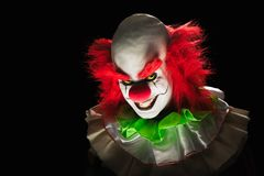 Scary clown on a dark background. High contrast image of a scary clown on a black background royalty free stock image