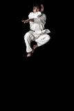 High Contrast karate young male fighter jump. Ing on black background stock photography