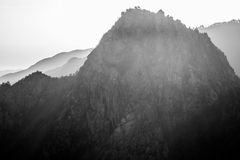 High contrast mountain with sharp edge, black and white with smokey background. Sharp steep mountain tree line B&W into sun giving dark foreground mountain and Stock Photos