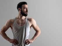 High contrast portrait of young fit bearded man with hands on hips looking away Royalty Free Stock Photography