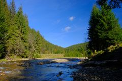 A high contrast shot of mountain river on sunny day. With deep blue sky color in Carpathian mountains, Ukraine Stock Photo
