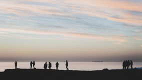 High contrast silhouettes of people at the beach facing the ocean on the horizon. Large boats in the background horizon, cloudy sky, Carcavelos Beach, Portugal royalty free stock photo