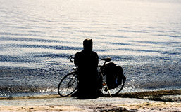 High contrast styled fisherman silhouette with retro bicycle on the beach Stock Images