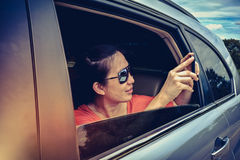 High contrast of traveler capturing a perfect road trip moment o. High contrast of happy asian woman holding mobile phone and taking photos in the car. Traveler Royalty Free Stock Image