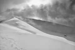 High-contrast winter mountain landscape. Winter mountain landscape partially sunlit. Cloudy skies. Black and white. Lenzerheide, canton Graubunden, Swiss Alps Royalty Free Stock Image