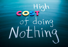 High cost of doing nothing. Conceptual words on blackboard Royalty Free Stock Images