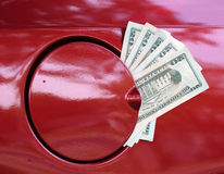 High Cost of Gas. Twenty dollar bills protruding from automobile gas cap illustrating the high cost of gas Stock Photo
