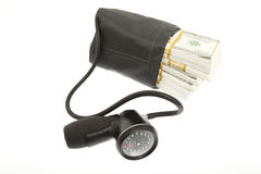 High cost of healthcare. Sphygmomanometer with bundles of cash Stock Photos
