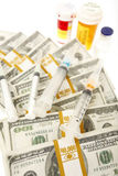 High cost of healthcare. Prescription bottles, syringes, and bundles of cash Royalty Free Stock Image