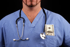 The high cost of healthcare. Doctor or nurse with stethoscope and 100 dollar bill in pocket Royalty Free Stock Image