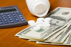 High Cost of Healthcare. Open bottle of pills on top of money, focus on bottom pills and calculator Stock Photos
