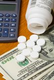 High Cost of Healthcare. Open bottle of pills on top of money, focus on bottom pills and calculator Royalty Free Stock Image