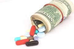 High Cost of Healthcare. Money rolled up with Pills flowing out, high costs of, expensive medication Royalty Free Stock Photos