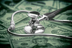 High cost of healthcare concept. Stethoscope over money as a concept for rising healthcare costs Royalty Free Stock Images