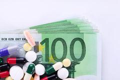 High Cost of Healthcare. Pills of different colors on money background Royalty Free Stock Photos
