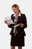 High cost of living. Attractive blond caucasian woman wearing a black business suit with tie holding an open envelope and a letter staring at it with an angry stock photos