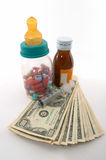 High cost of medical bills for children. High costs of children medication, bottle & pills, tall perspective and apparent tall bottle emphasizes high cost Stock Photography