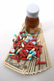 High cost of medical bills, tall perspective. High costs of medication, bottle & pills, top view, tall perspective and apparent tall bottle emphasizes high cost Royalty Free Stock Photos