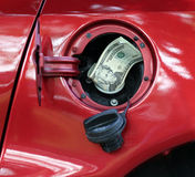 High Cost of Oil. Money sticking out of automobile fuel tank opening signifying and illustrating the high cost of gas stock image