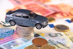 High costs concept for car maintenance, leasing, transportation. Toy car on a stack of euro coins, concept image for buying, renting, fuel or service and repair royalty free stock photo