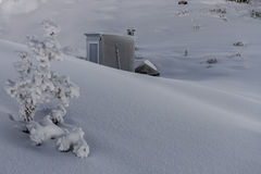 High country hut in deep snow. Hut in the mountains, fresh snow with a blue bird day. Location Kaikoura, New Zealand Royalty Free Stock Photography