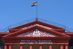 High court. The facade of the Karnataka state of India high court building in Bangalore with indian flag Stock Photos