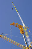High cranes. Couple of high construction cranes on a blue sky background Royalty Free Stock Photos