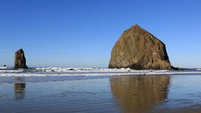 High definition 1080p zooming out movie of beautiful Cannon Beach with its well-known Haystack Rock landmark and Needles located n. Ear Tolovana Park in Oregon stock video